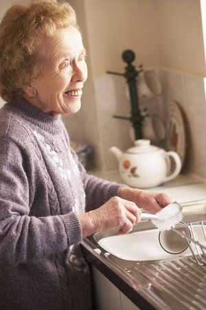 Senior Woman Washing Up At Sink Stock Photo - 5043423