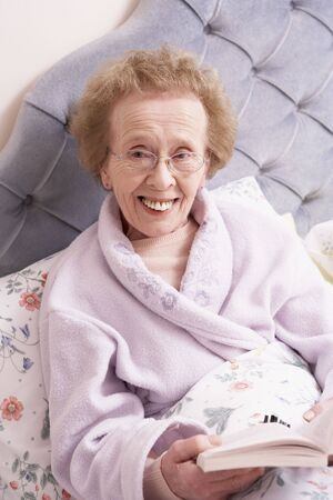 Senior Woman Relaxing In Bed With Book Stock Photo - 5041520