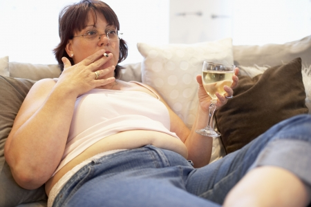overeating: Overweight Woman Relaxing On Sofa