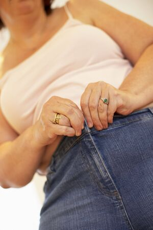fasten: Overweight Woman Trying To Fasten Trousers Stock Photo