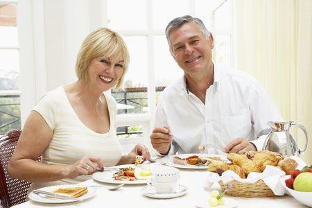 Middle Aged Couple Enjoying Hotel Breakfast photo