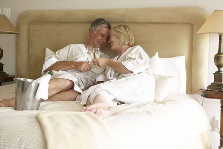 Middle Aged Couple Enjoying Champagne In Bedroom photo