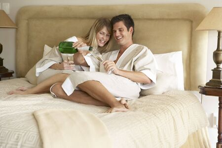 Young Couple Enjoying Champagne In Bedroom photo