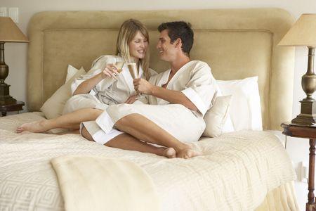 brindisi champagne: Coppia giovane gode di champagne in camera da letto