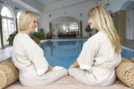 Two Women Relaxing By Swimming Pool Stock Photo - 5043395