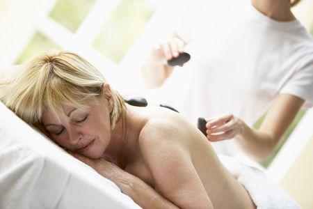 Middle Aged Woman Enjoying Hot Stone Treatment photo