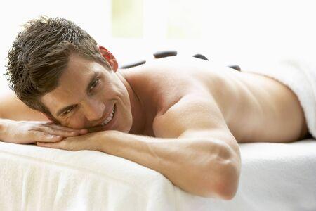 homme massage: Young Man Enjoying traitement aux pierres chaudes