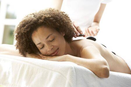 massage table: Young Woman Enjoying Hot Stone Treatment