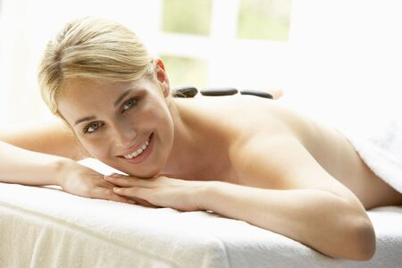 Young Woman Enjoying Hot Stone Treatment photo