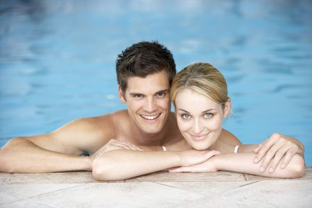 Young Couple Swimming In Pool photo