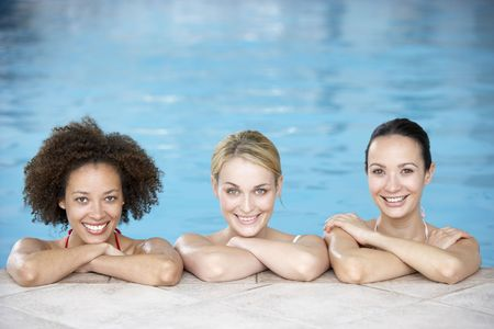 Three Female Friends In Swimming Pool Stock Photo