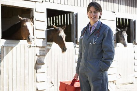 vetinary: Portrait Of Vet Standing By Horse Stables Stock Photo