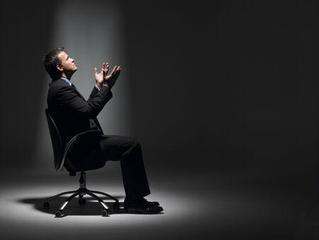 Businessman Sitting In Spotlight photo