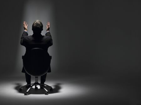 to beg: Businessman Sitting In Spotlight