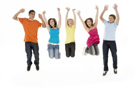 Group Of Five Young Children Jumping In Studio photo