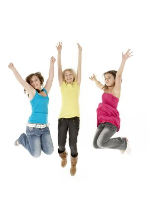casual clothing 12 year old: Group Of Three Young Girls Leaping In Air Stock Photo