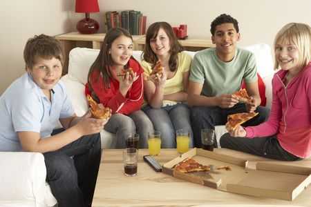 casual clothing 12 year old: Group Of Children Eating Pizza At Home