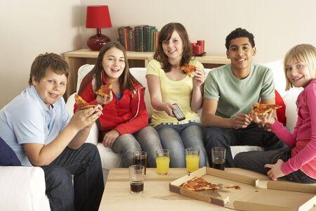 ni�os comiendo: Grupo de ni�os comer pizza ver televisi�n Foto de archivo