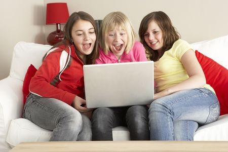 12 13: Group Of Three Girls Using Laptop At Home