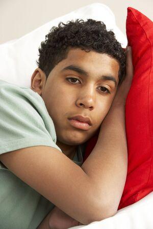 Young Boy Looking Sad On Sofa photo