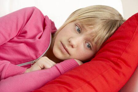 preteen girl: Young Girl Looking Sad On Sofa Stock Photo