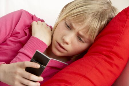 cyber bullying: Young Girl Reading Text And Looking Worried