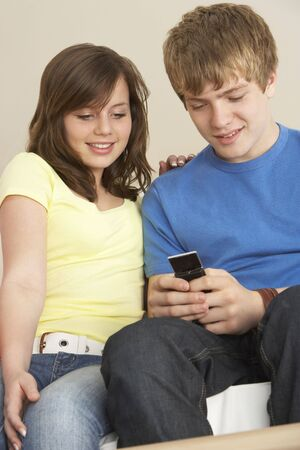 boy 12 year old: Teenage Couple Reading Text Message Stock Photo