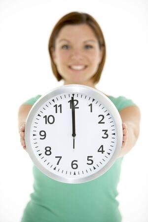o�??clock: Woman holding Listado de las 12 en punto del reloj Foto de archivo