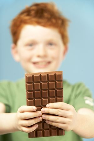 Young Boy Holding Bar Of Chocolate Stock Photo