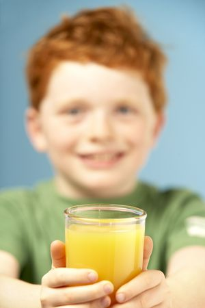 Young Boy Holding Glass Of Juice