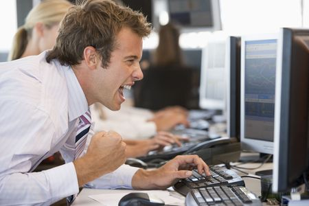 deal in: Stock Trader Overjoyed Looking At Monitor Stock Photo