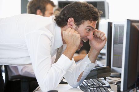 success man: Stock Trader Overjoyed Looking At Monitor Stock Photo