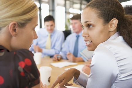 each: Businesswomen Talking To Each Other During Meeting