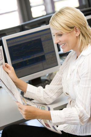 tilt views: Businesswoman Reading Newspaper At Work Desk