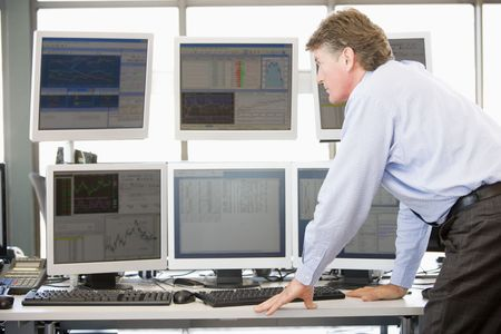 trader: Stock Trader Examining Computer Monitors Stock Photo