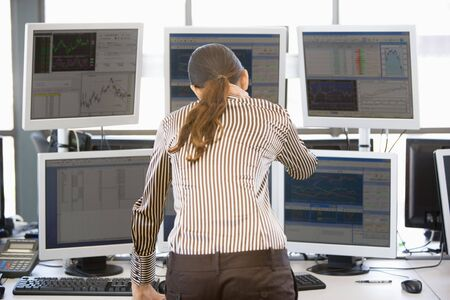 stock traders: Stock Trader Looking At Multiple Monitors