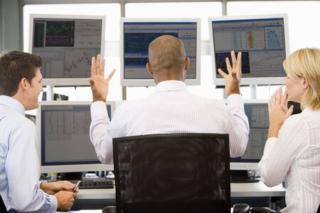 backview: Stock Traders Viewing Monitors