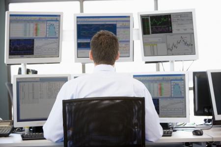 makler: Stock Trader Blick in die mehrere Monitore  Lizenzfreie Bilder