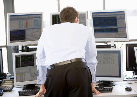 agente comercial: Stock Trader Mirando a varios monitores