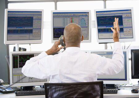 agente comercial: Stock Trader Talking animadamente en el tel�fono  Foto de archivo