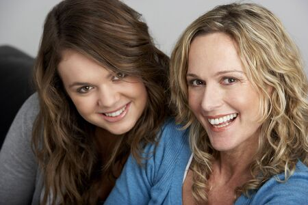 Mother And Daughter Sitting On Sofa photo