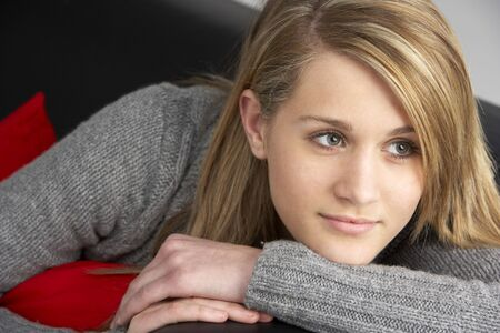 Teenage Girl Sitting On Sofa photo