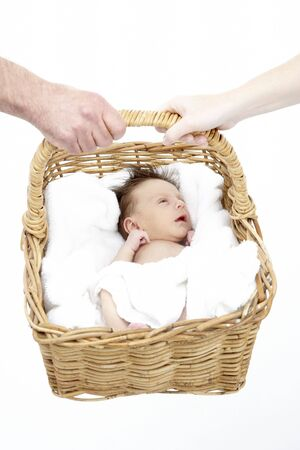Newborn Baby Held In Basket By Parents photo