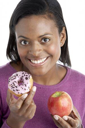 Woman Choosing Between Apple And Doughnut photo