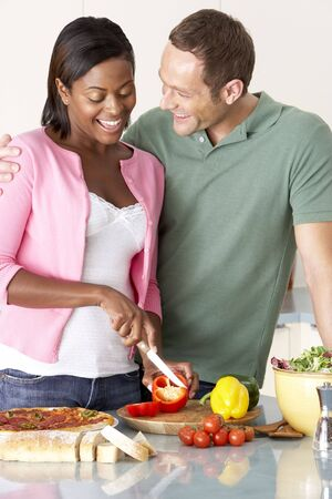 Young Couple Preparing Meal In Kitchen photo