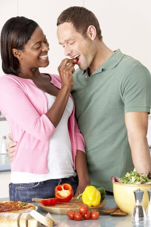 vegetables young couple: Young Couple Preparing Meal In Kitchen