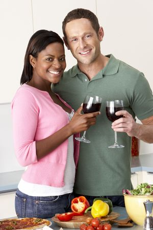 vegetables young couple: Young Couple Enjoying Glass Of Wine In Kitchen