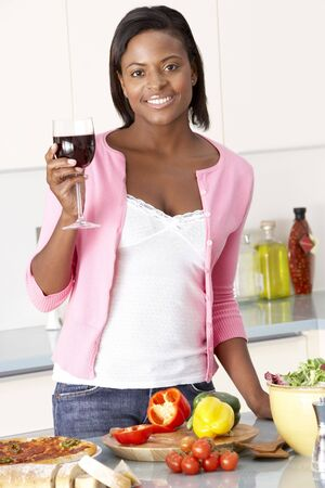 Woman Enjoying Glass Of Wine In Kitchen photo