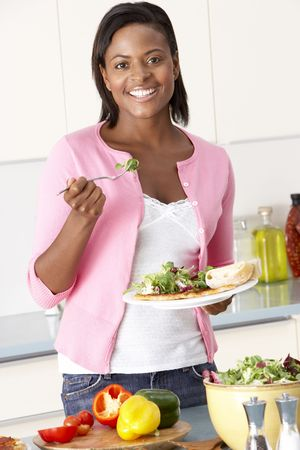 serving food: Woman Eating Meal In Kitchen Stock Photo