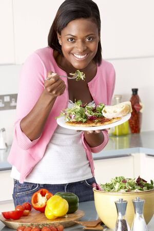 preparing food: Woman Eating Meal In Kitchen Stock Photo